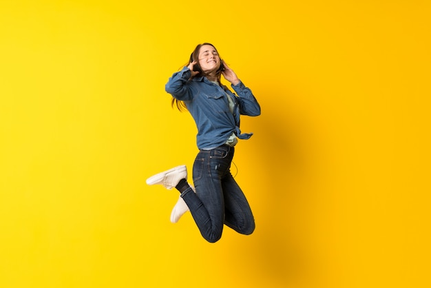 Jonge vrouw die over op geel springt