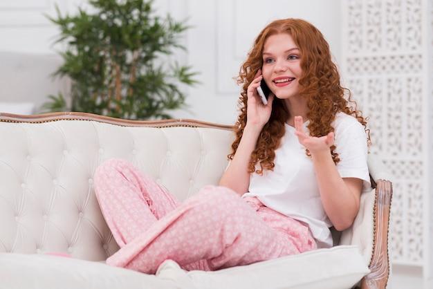 Jonge vrouw die over telefoon spreekt