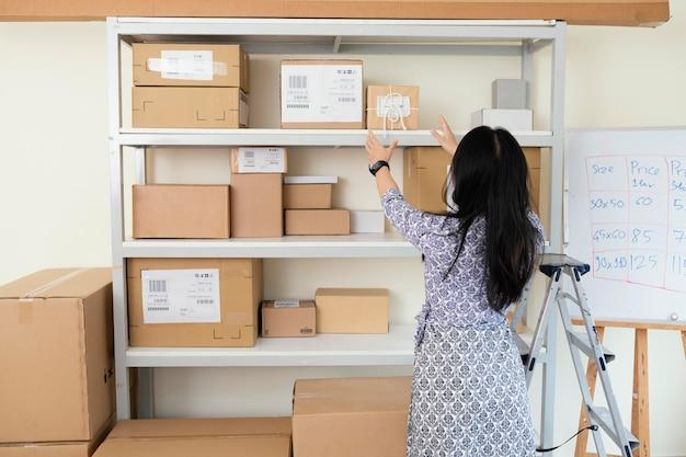 Jonge vrouw die pakket neemt en hen voor levering voorbereidt