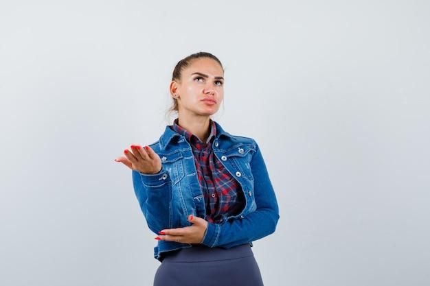Jonge vrouw die palm in geruit overhemd, jeansjasje uitspreidt en weemoedig, vooraanzicht kijkt.