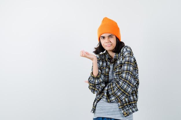 Jonge vrouw die palm in oranje hoed en geruit overhemd uitspreidt en ontevreden kijkt