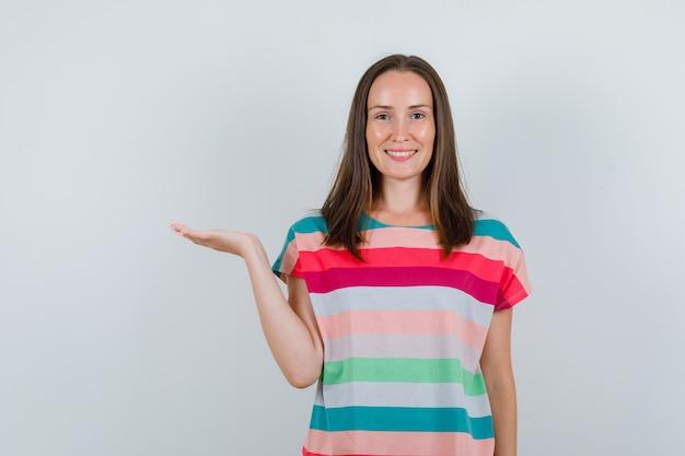 Jonge vrouw die palm opheft als iets in t-shirt vangen en blij, vooraanzicht kijken.