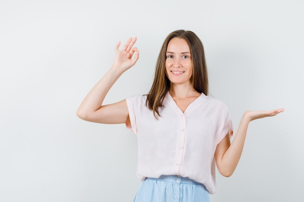 Jonge vrouw die palm opzij spreidt met ok gebaar in t-shirt, rok en positief, vooraanzicht kijkt.