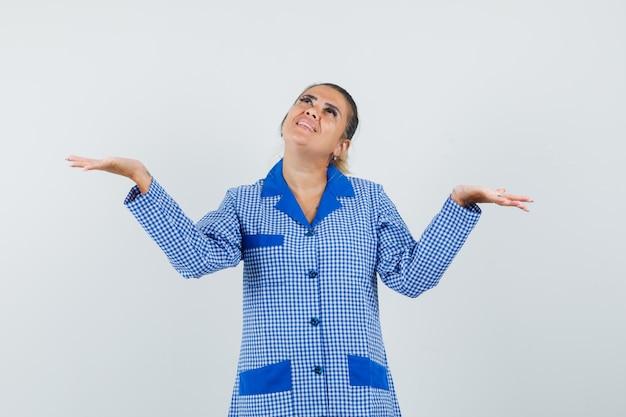 Jonge vrouw die palmen spreidt als iets groots in het blauwe overhemd van de gingangpyjama vasthoudt en er gelukkig uitziet. vooraanzicht.
