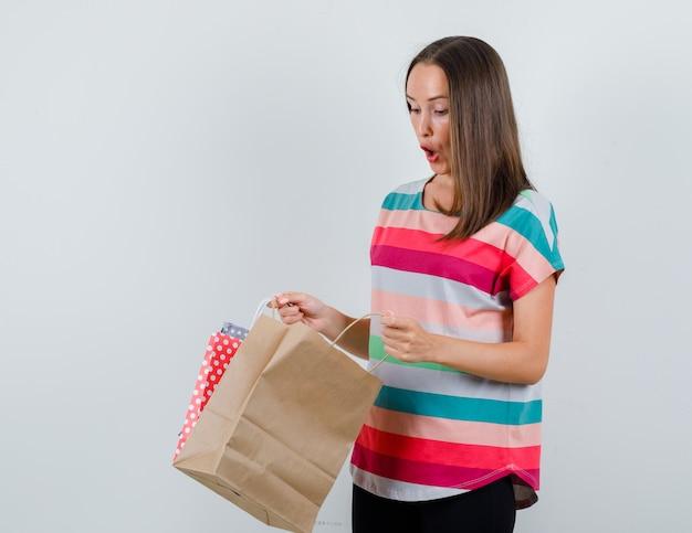 Jonge vrouw die papieren zak in t-shirt, broek onderzoekt en verbaasd, vooraanzicht kijkt.