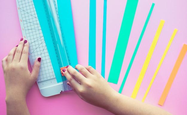 Jonge vrouw die papierkunst maakt in kleurrijk met roze ruimte