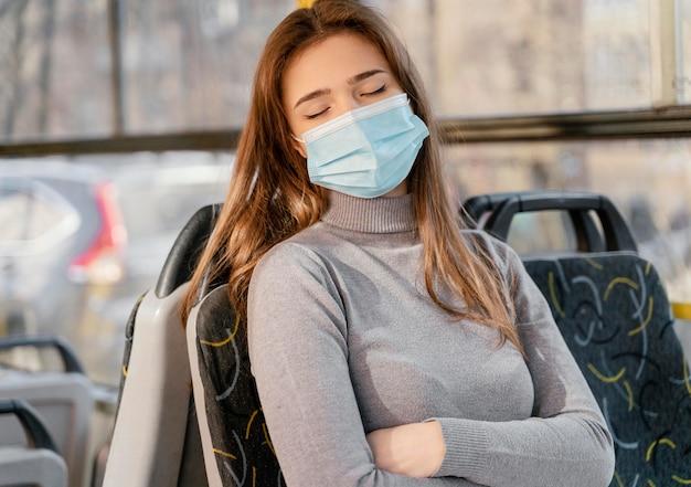 Jonge vrouw die per stadsbus met chirurgisch masker reist