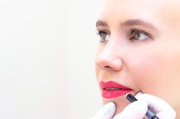 Jonge vrouw die permanente make-up op haar lippen bij de schoonheidsspecialisten salon. permanente make-up (tatoeage). een contour tekenen met een wit lippotlood