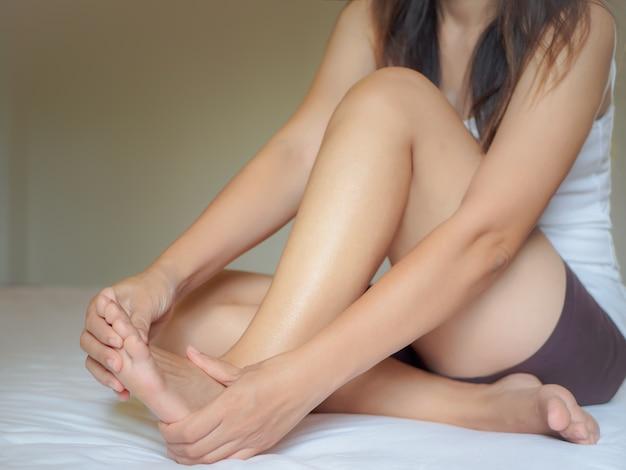 Jonge vrouw die pijn in haar voet thuis voelt. gezondheidszorg en medisch concept.