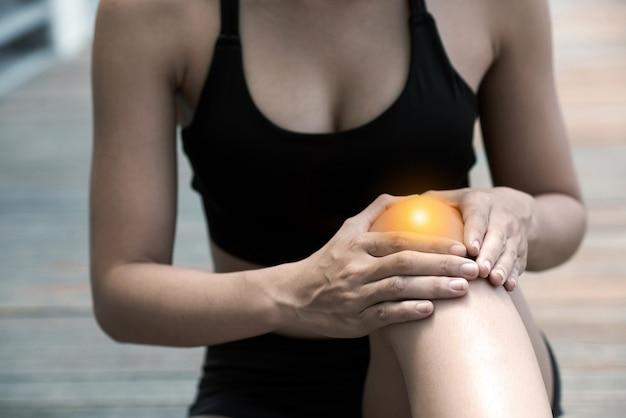 Jonge vrouw die pijnlijke knie aanraakt