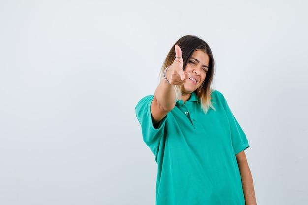 Jonge vrouw die pistoolgebaar naar camera in polot-shirt toont en er vrolijk uitziet, vooraanzicht.