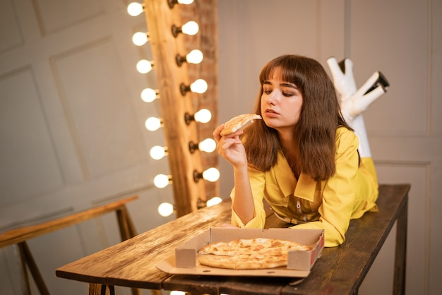 Jonge vrouw die pizzazitting in gele kombineh eet