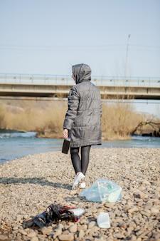 Jonge vrouw die plastic afval van het strand verzamelt en het in zwarte plastic zakken voor kringloop zet. reiniging en recycling concept.