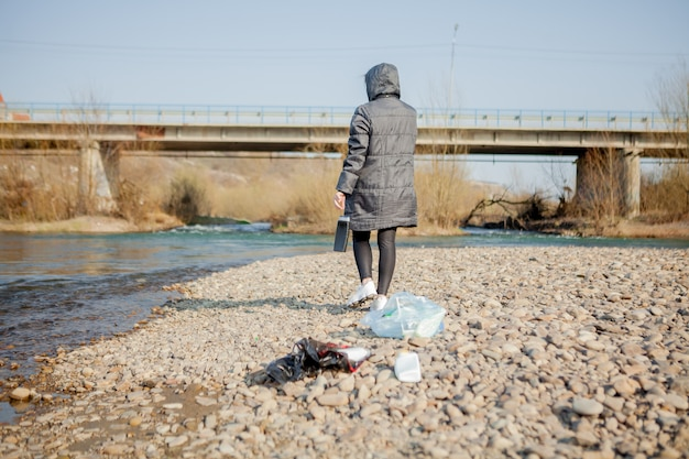 Jonge vrouw die plastic afval van het strand verzamelt en in zwarte plastic zakken doet