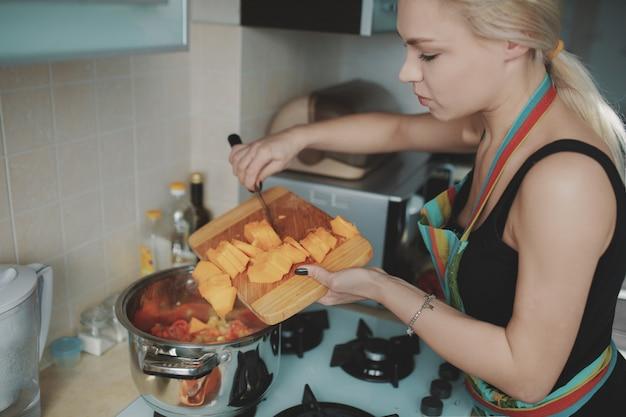 Jonge vrouw die pompoensoep voorbereidt