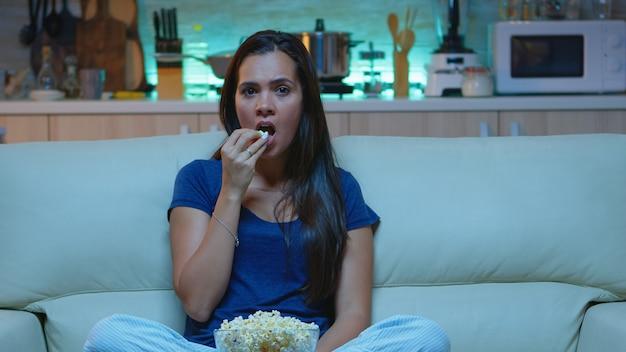 Jonge vrouw die popcorn eet en naar een interessante serie op tv kijkt. geschokt geconcentreerd verbaasd alleen thuis 's nachts dame met verrast gezicht kijkend naar een spannende film zittend op een comfortabele bank