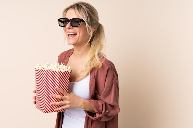 Jonge vrouw die popcorns over geïsoleerde achtergrond eet