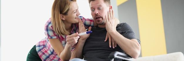 Jonge vrouw die positieve zwangerschapstest toont aan gehandicapte man in rolstoel