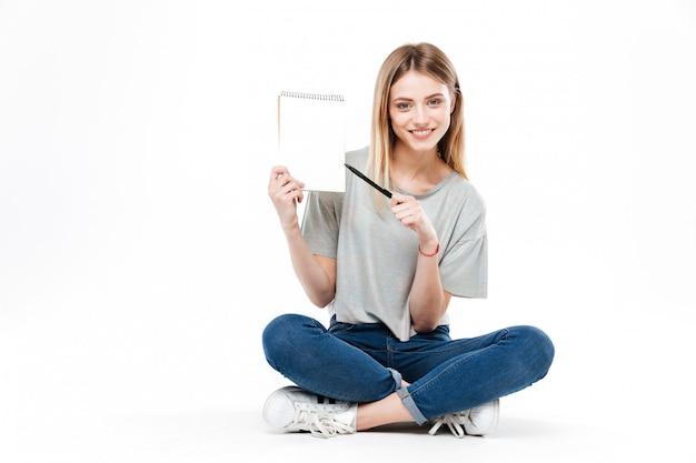 Jonge vrouw die potlood en notitieboekje gebruiken