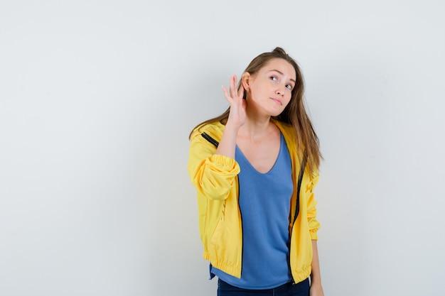 Jonge vrouw die privégesprek in t-shirt, jas afluistert en er nieuwsgierig uitziet. vooraanzicht.