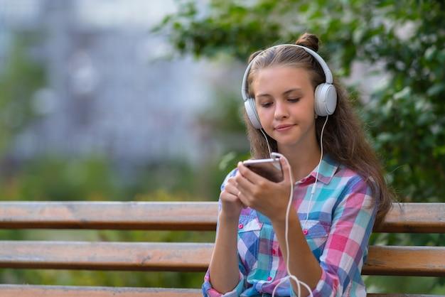 Jonge vrouw die probeert te beslissen over een nieuwe soundtrack die met een bedachtzame uitdrukking naar haar mobiele telefoon kijkt terwijl ze buiten naar muziek luistert