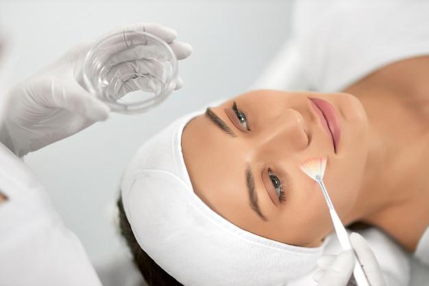 Jonge vrouw die procedure voor gezicht in schoonheidsspecialiste doet