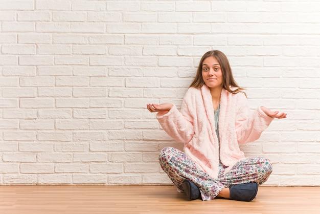Jonge vrouw die pyjama draagt die en schouders twijfelt ophaalt