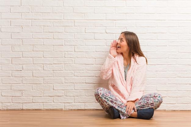 Jonge vrouw die pyjama draagt die roddel ondertiteling fluistert