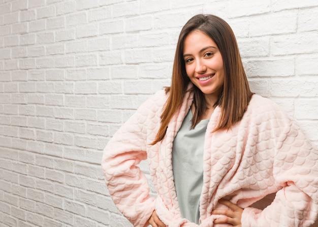 Jonge vrouw die pyjama met handen op heupen draagt