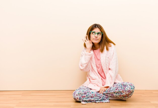 Jonge vrouw die pyjama's draagt die thuis ernstig en nieuwsgierig zitten kijken