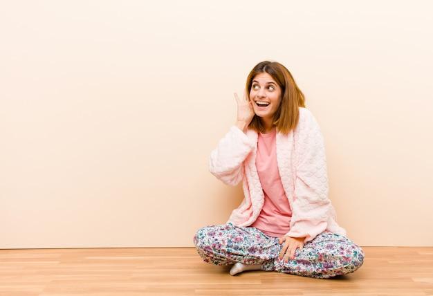 Jonge vrouw die pyjama's draagt die thuis glimlachen, nieuwsgierig aan de kant kijken, proberen te roddelen of een geheim afluisteren