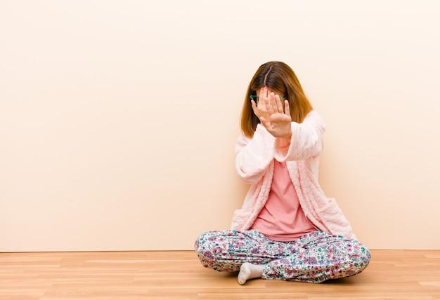 Jonge vrouw die pyjama's draagt die thuis zitten die gezicht behandelen met hand en andere hand vooraan zetten om camera tegen te houden, die foto's of beelden weigeren