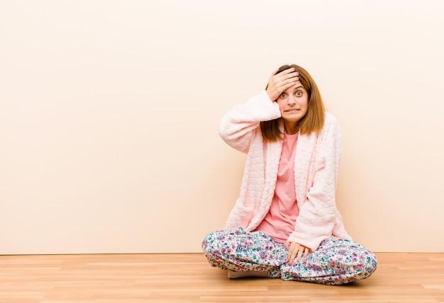 Jonge vrouw die pyjama's draagt die thuis zitten in paniek over een vergeten deadline, zich gestrest voelen, een puinhoop of een fout moeten verbergen
