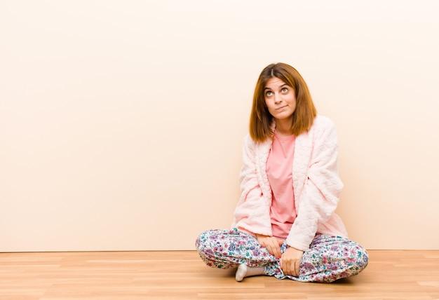 Jonge vrouw die pyjama's draagt die thuis zitten in verwarring gebracht en verward, benieuwd zijnd of proberen een probleem op te lossen of het denken