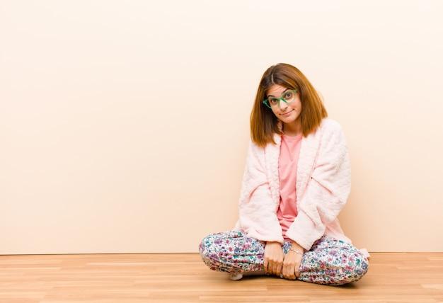 Jonge vrouw die pyjama's draagt die thuis zitten met een goofy gekke verbaasde uitdrukking wangen puffend voelen en vol voedsel