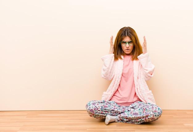 Jonge vrouw die pyjama's draagt die thuis zitten schreeuwen met handen omhoog in de lucht, woedend, gefrustreerd, gestrest en overstuur voelen