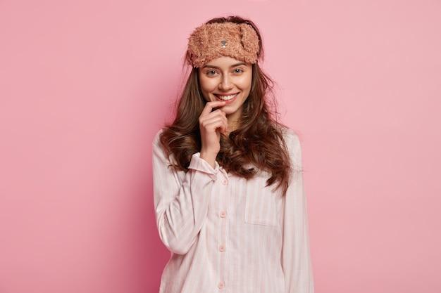 Jonge vrouw die pyjama's en slaapmasker draagt