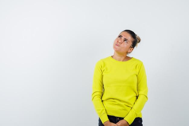 Jonge vrouw die rechtop staat, naar boven kijkt en voor de camera poseert in gele trui en zwarte broek en peinzend kijkt