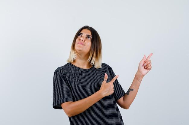 Jonge vrouw die rechtsboven met wijsvingers in zwarte kleding richt en gericht kijkt. vooraanzicht.