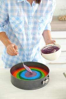 Jonge vrouw die regenboogcake in keuken maakt