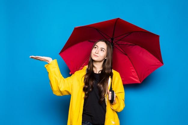 Jonge vrouw die regenjas draagt die kleurrijke paraplu over blauwe muur houdt