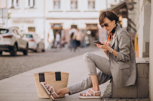 Jonge vrouw die reist en telefoon gebruikt