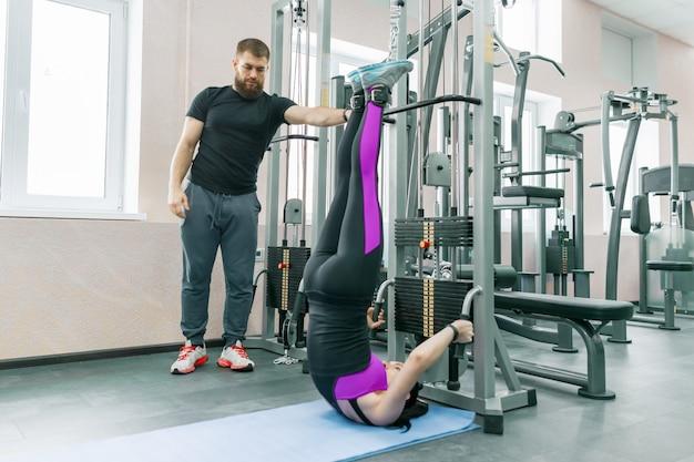 Jonge vrouw die revalidatieoefeningen met persoonlijke instructeur doet