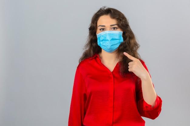 Jonge vrouw die rode blouse in medisch beschermend masker draagt dat camera bekijkt en vinger aan masker op gezicht over geïsoleerde witte achtergrond richt