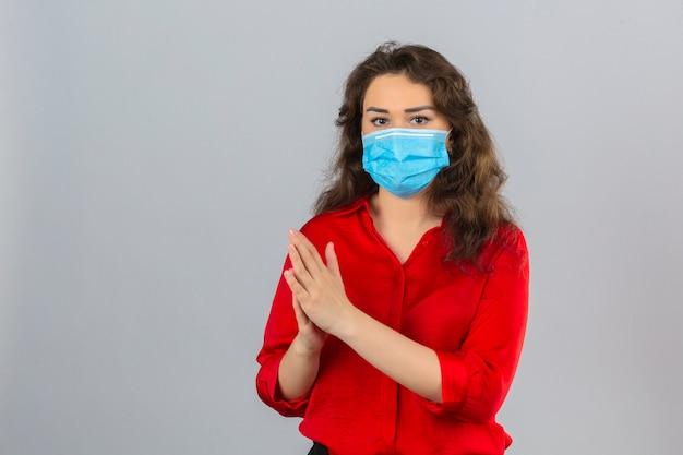 Jonge vrouw die rode blouse in medisch beschermend masker draagt die camera bekijkt die handen over geïsoleerde witte achtergrond wrijft