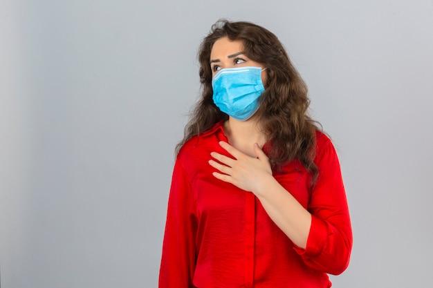 Jonge vrouw die rode blouse in medisch beschermend masker draagt die onwel en ziek kijkt met hand op borst over geïsoleerde witte achtergrond