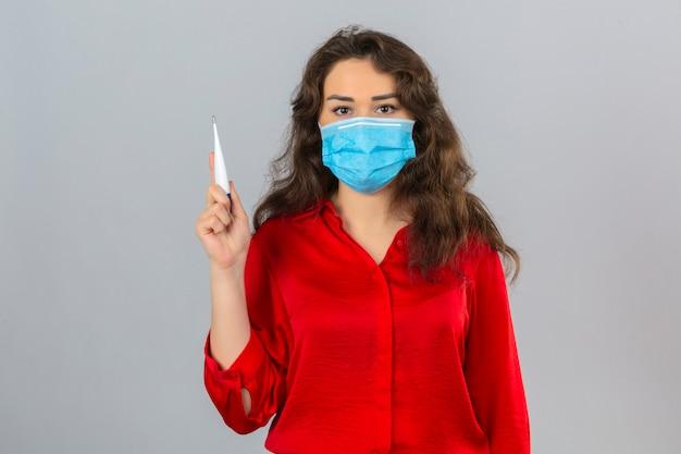 Jonge vrouw die rode blouse in medisch beschermend masker draagt die zich met digitale in hand thermometer bevindt die camera met ernstig gezicht bekijkt over geïsoleerde witte achtergrond