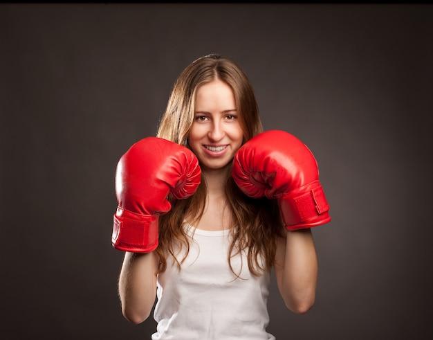 Jonge vrouw die rode bokshandschoenen draagt