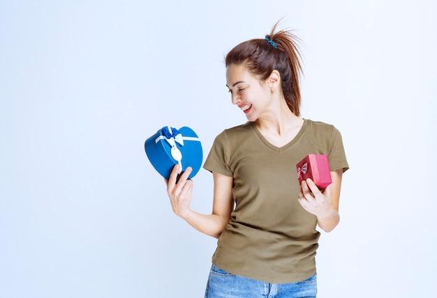 Jonge vrouw die rode en hartvormige blauwe geschenkdozen vasthoudt en ervan geniet