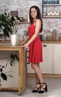 Jonge vrouw die rode kleding en zwarte schoenen draagt die zich bij de keuken bevinden